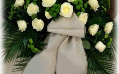 Bēru vainags - zaļas krizantēmas un baltas rozes uz zaļu augu pamatnes ar bēšīga auduma lentu