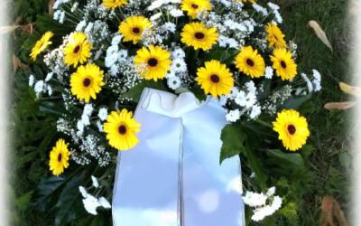 Bēru vainags - dzeltenas gerberas un baltas krizantēmas uz zaļu augu pamatnes ar baltu lentu