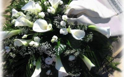 Bēru vainags - baltas kallas, baltas lizantes un ģipsene uz zaļu augu pamatnes ar bēšigu auduma lentu