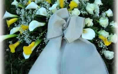 Bēru vainags - dzeltenas, baltas kallas, baltas rozes un ģipsene uz zaļu augu pamatnes ar bēšigu auduma lentu