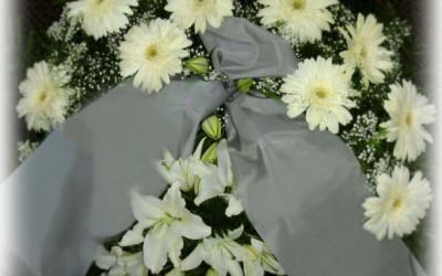 Bēru vainags - baltas gerberas, baltas lilijas un ģipsene uz zaļu augu pamatnes ar gaišu lentu
