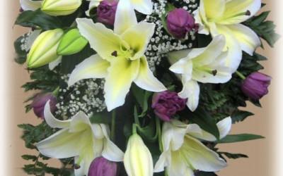Bēru štrauss - baltas lilijas un violetas tulpes uz zaļu augu pamatnes