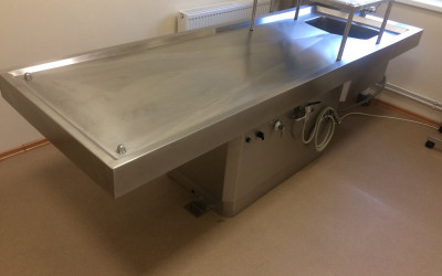 Autopsiju (sekciju) galds. Pirms atvadu ceremonijas veic mirušās personas apkopšanu. Nodrošina sagatavošanas procedūras, nomazgā, uzliek grimu, apģērbj, iezārko u.tml.