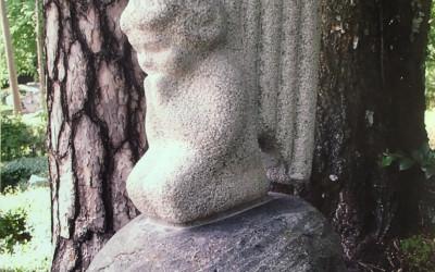 Viegli nolaidies gaišs bērna enģelis ar lūgšanā uz leju noliegtu galvu. Formas plastika pārejoša un plūstoša, virsma - bučardēta.