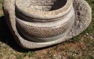 Puķupods ar greznu siluetu un dekoratīvu jostas līniju lieliski izceļas uz bučardētā un plēstā granīta fona.