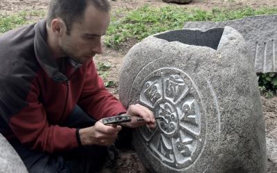 Roku darbs un eksotisks raksts Latvijas laukakmenim, tēlnieka R. Jaunzema izpildījumā.